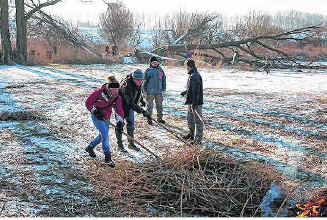 Vrijwilligers maaien riet op bevroren grachten