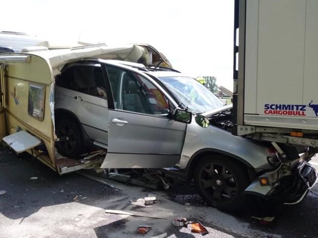 Koppel met caravan gesandwicht tussen vrachtwagens op E313