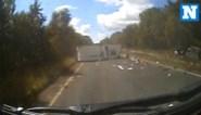 Bestuurder en zijn hondje zwalpen aan hoge snelheid met caravan over de weg en gaan meermaals overkop