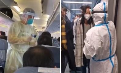 Medisch personeel in witte pakken screent vliegtuigpassagiers op symptomen dodelijk virus