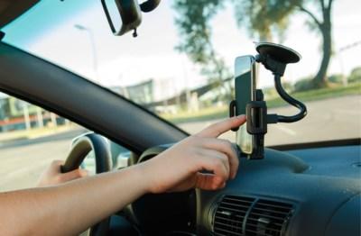 Je mag je telefoon niet vasthouden tijdens het rijden, maar krijg je ook een boete voor sms'en in de file of je telefoon als gps gebruiken?