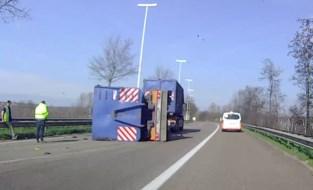Aanhangwagen geladen met bobcat kantelt op expresweg