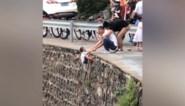 Chinese man laat kind over klif hangen om foto's te nemen