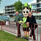 Marc Claerhout en schepen Dominique Windels poseren met de grote glimlach met de mascotte op de plaats waar ook de komende jaren aankomstlijn van E3 Harelbeke zal liggen.