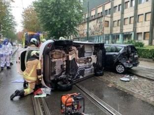 Auto kantelt om na botsing tegen twee geparkeerde wagens