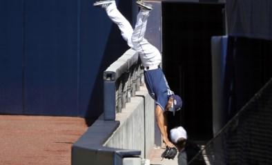 Straffe beelden uit het baseball: speler vangt bal in duikvlucht over betonnen balustrade van het stadion