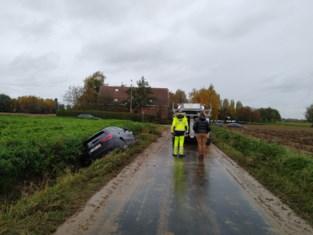 Automobiliste glijdt in gracht door modder op de weg