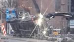 Vrachtwagen met betonpomp kantelt in bouwput