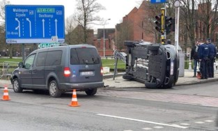 Wagen belandt op zijkant na zware klap, vangrail brengt redding