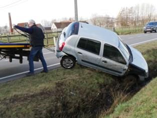 Auto belandt in diepe gracht, bestuurster geklemd