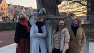 Meer vrouw op straat steekt mannelijke standbeelden in een kleedje