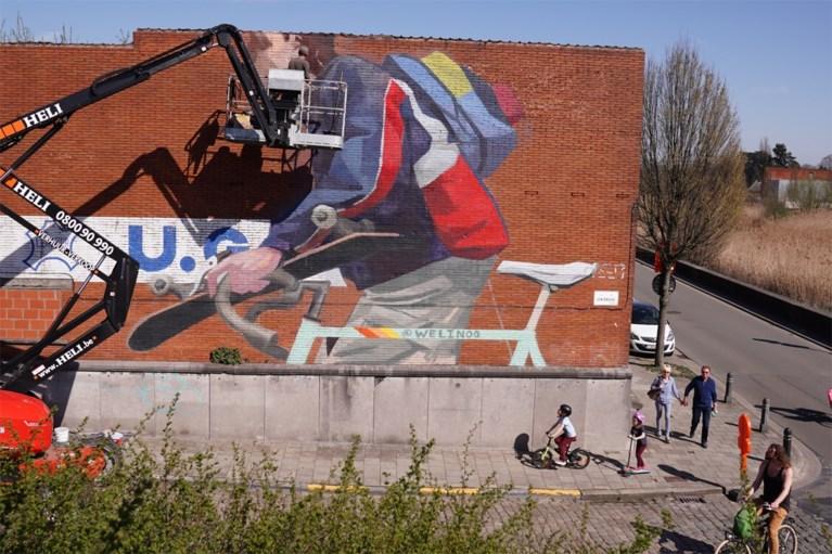 Straatkunst in Gentbrugge: enorme fietser met skateboard prijkt naast drukke brug