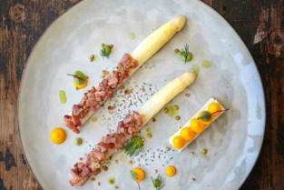 Gelaagde rauwe asperge met lardo, gekookte asperges met spek