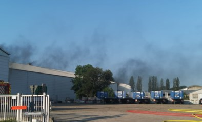 Brand in bouwbedrijf naast E17, zwarte rookpluim van ver zichtbaar
