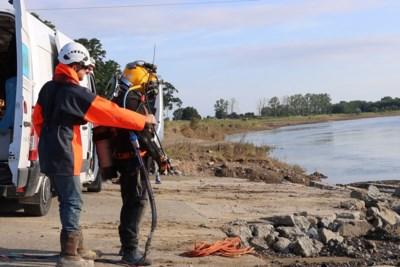 Duikers zoeken naar weggevaagde straat van veerpont in Maas, minister inspecteert Maasbrug